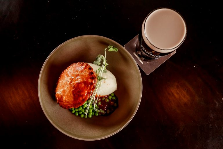 A photograph of a pint of Guinness alongside a steak pie and sausages being served at Finn McCool's Irish Pub.